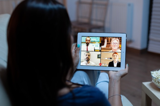 Vrouw luisteren online training op tablet 's avonds laat zittend op de bank