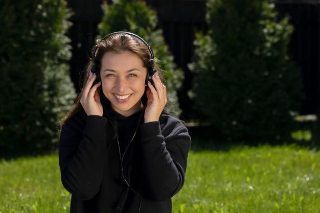 Vrouw luistert naar muziek met een koptelefoon zittend op een groen gazon in de tuin bij het huis. rust op gazonconcept. ontspannen op groen gras. warme zonnige zomerdag.