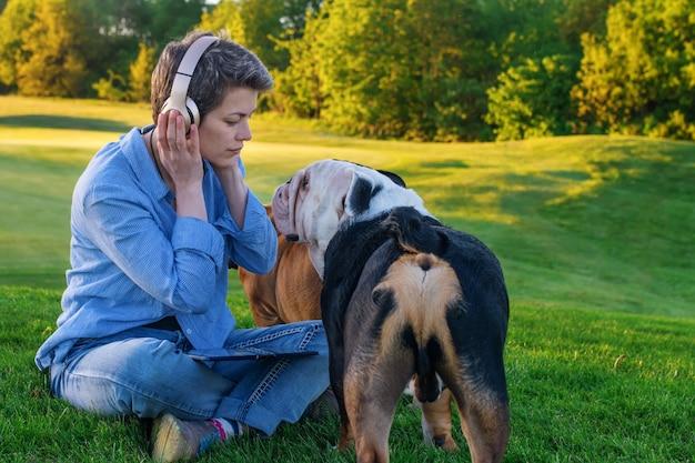 Vrouw luistert naar muziek of audioboek, kijkt naar de hond en zit op groen gras in het park
