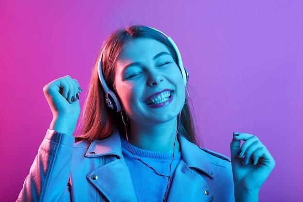 Vrouw luistert naar muziek via koptelefoon, houdt de ogen gesloten en blij lachend, met vuisten omhoog geïsoleerd boven roze neonruimte