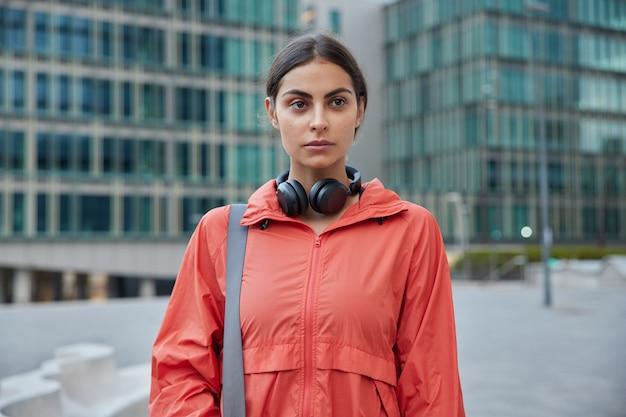 Vrouw luistert online naar radio tijdens trainingspauze gebruikt geluidsaccessoire houdt fitnessdoelen overdag wandelingen in de stad denkt na over haar toekomstige sportleven wil fitnessinstructeur worden