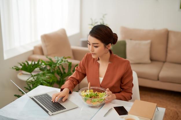 Vrouw lunchen uit glazen kom en met behulp van laptop.