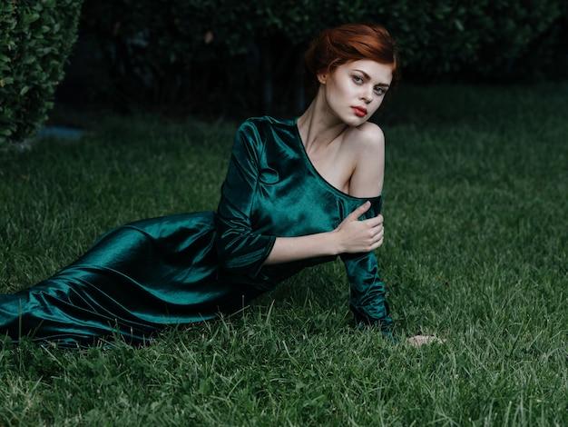 Vrouw luxe groene jurk ligt op het gras prinses carnaval