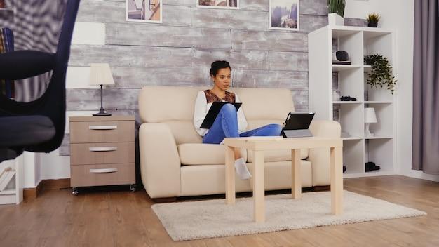 Vrouw maakt aantekeningen op het klembord tijdens een videogesprek terwijl ze thuis werkt.