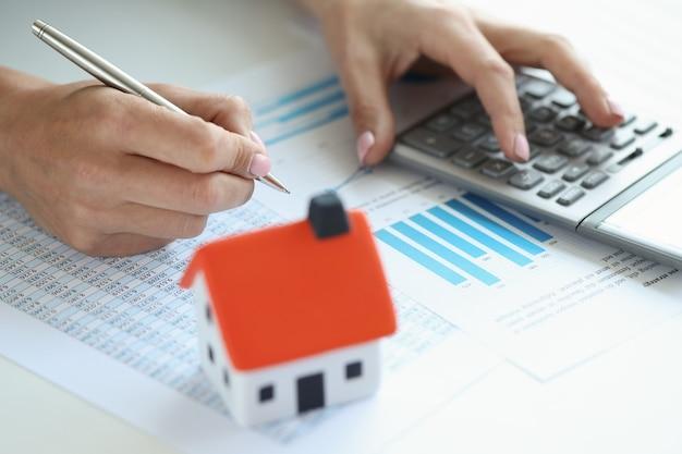 Vrouw maakt berekeningen op rekenmachine voor het kopen van een huis op krediet financiële documenten voor