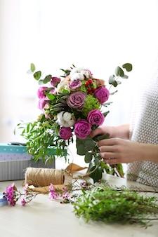 Vrouw maakt een boeket bloemen