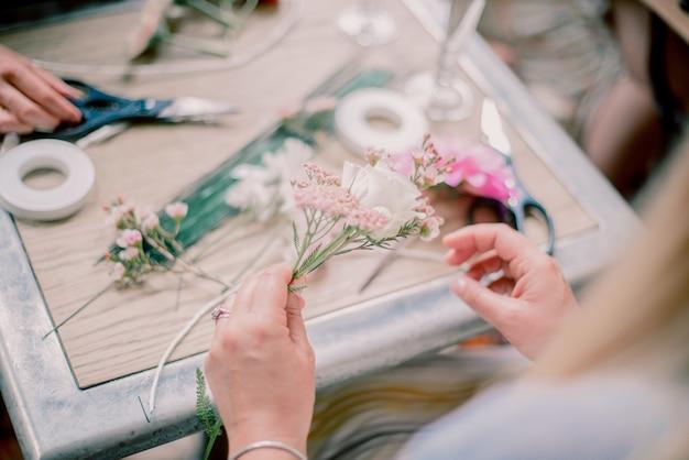 Vrouw maakt een decoratie met bloemen