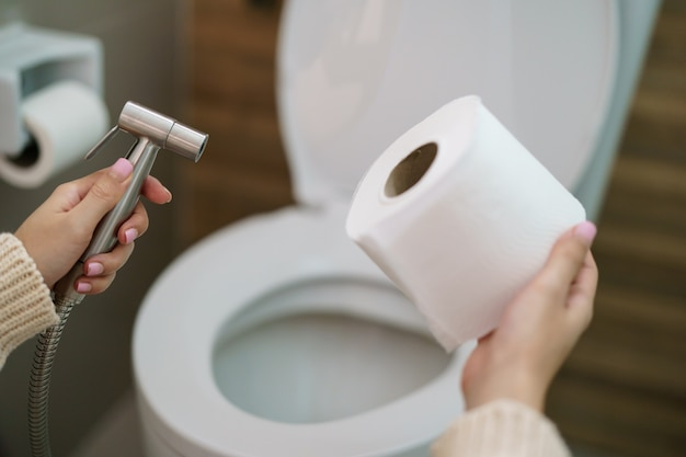 Vrouw maakt een keuze, bidetdouche of toiletpapier.