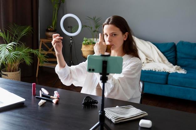 Vrouw maakt een make-up vlog met haar smartphone