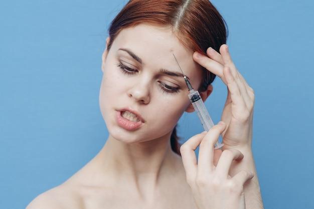 Vrouw maakt een verjongende injectie in het gezicht op een blauwe en een spuit met een botox-naald