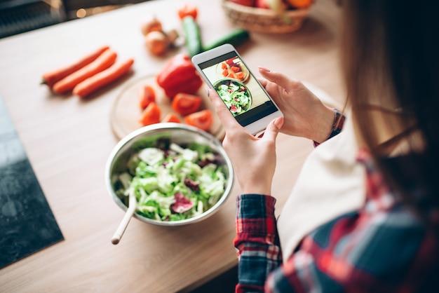 Vrouw maakt foto van plantaardige salade kookproces op de keuken. bereiding van verse dieetvoeding. vrouw bereidt een romantisch diner voor haar man