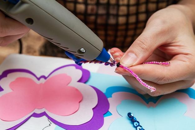 Vrouw maakt gebruik van hotmelt lijmpistool in handgemaakte toepassingen
