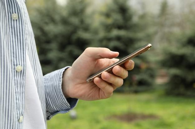 Vrouw maakt gebruik van smartphone. buitenfoto in park