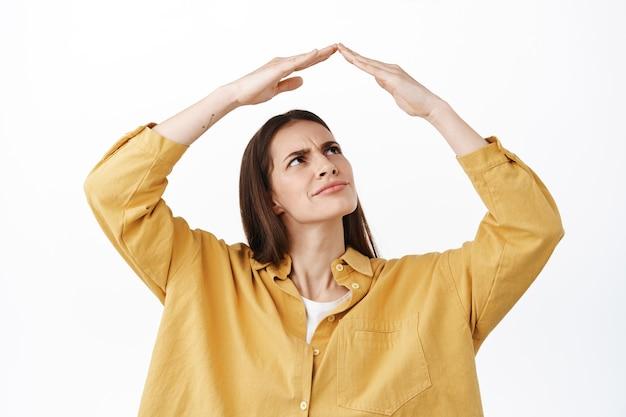 Vrouw maakt handgebaar op het dak en staart verward of twijfelachtig naar haar dak, verbijsterd fronsend, verbaasd grimassend, staande tegen de witte muur