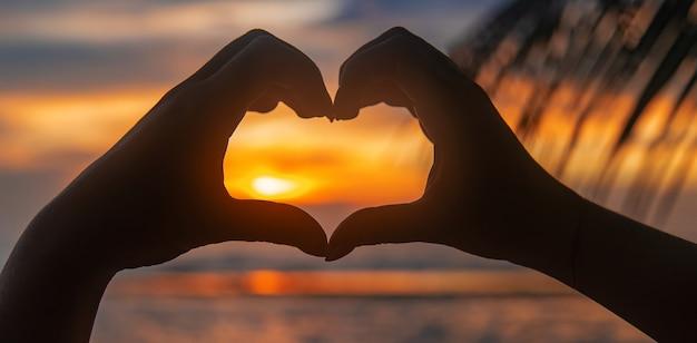 Vrouw maakt hart handen bij zonsondergang