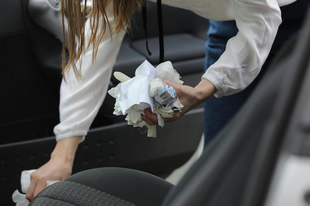 Vrouw maakt in haar auto schoon. interieur auto detaillering. reinigt de interieurauto. zeer verstopte auto. selectieve aandacht