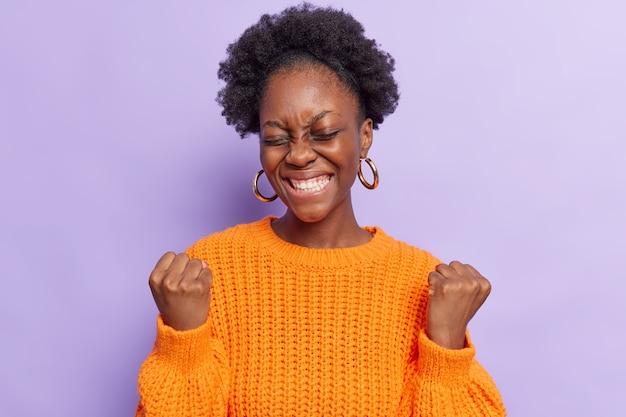 Vrouw maakt ja gebaar voelt als winnaar glimlacht breed viert overwinning voelt opgewonden houdt ogen gesloten draagt casual oranje gebreide trui geïsoleerd op paars