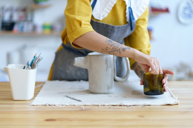 Vrouw maakt kleiservies in workshop jonge hipster artisanale werken bij keramische kruik in moderne studio