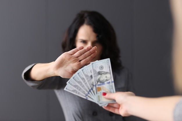 Vrouw maakt negatief gebaar voor geld dat aan haar wordt verstrekt. weigering van steekpenningen concept