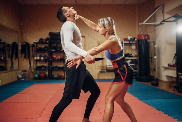Vrouw maakt punch op de keel, zelfverdedigingstraining met mannelijke personal trainer, sportschool interieur. vrouwelijke persoon op training, zelfverdedigingsoefening