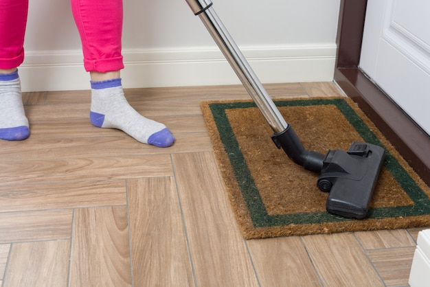 Vrouw maakt schoon met behulp van stofzuiger