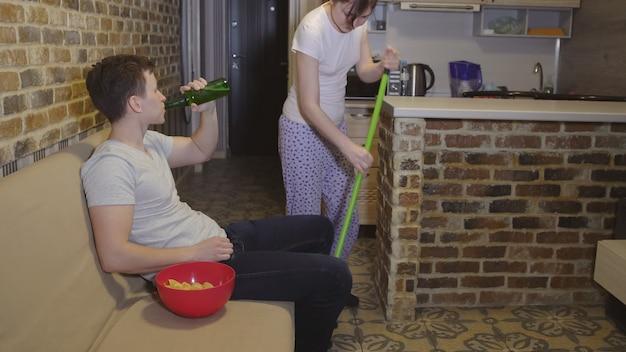 Vrouw maakt schoon, waardoor de man geen voetbal kan kijken.