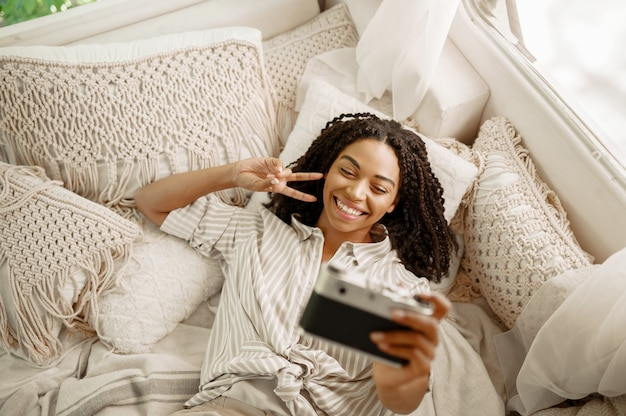 Vrouw maakt selfie in rv bed, bovenaanzicht, kamperen in een aanhangwagen. stel reist op busje, romantische vakanties op camper, camper vrije tijd in kampeerauto