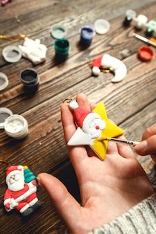 Vrouw maakt stijlvolle kerstcadeaus, schildert porseleinen beeldjes.