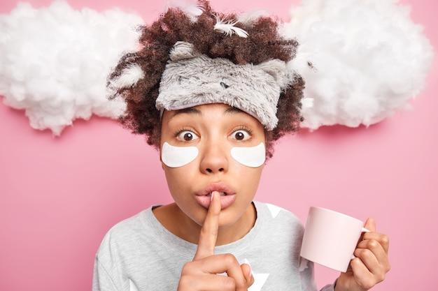 Vrouw maakt stil gebaar vertelt geheime drankjes koffie houdt mok heeft veren in krullend haar gekleed in pyjama poses op roze