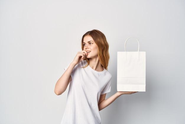 Vrouw maakt t-shirts met pakket in handen entertainment winkelen