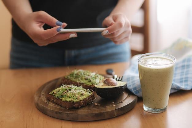 Vrouw maakt thuis foto van lunch. vrouwelijke glogger maakt voedselfotografie. gezond veganistisch eten. toast met avocado en smoothie met spinazie.