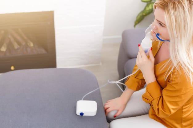 Vrouw maakt thuis inhalatievernevelaar. een masker vasthoudende vernevelaar dampen inademen spuit de medicatie in uw longen zieke patiënt. zelfbehandeling van de luchtwegen met behulp van inhalatievernevelaar