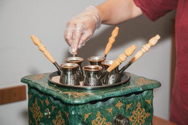 Vrouw maakt turkse koffie op een koffiezetapparaat met zand in cezve. oosterse, oosterse koffie.