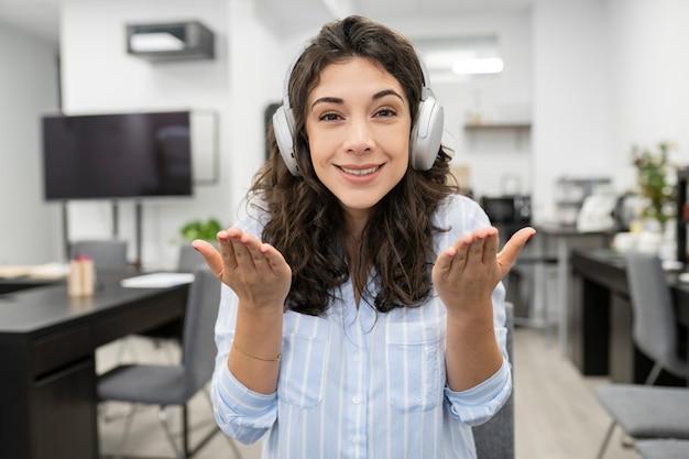 Vrouw maakt videogesprek op kantoor met koptelefoon, een vrouw met zwart haar en spaanse trekken