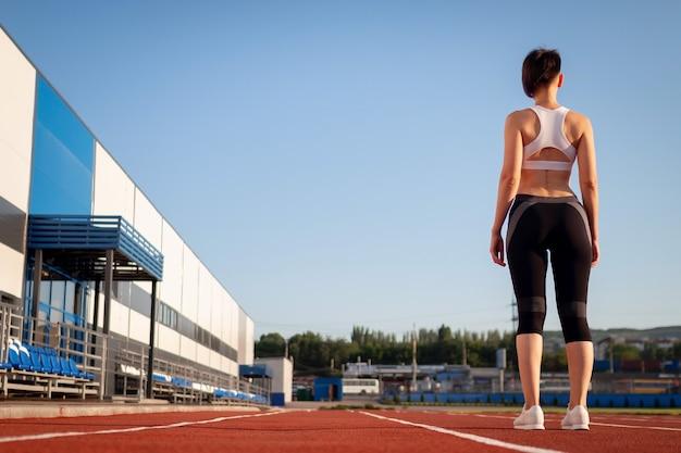 Vrouw maakt zich klaar om te beginnen op stadium, zomer buiten training. vrouw run training buitenshuis. gezondheid en sport concept.