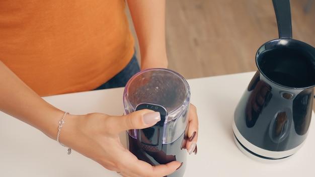 Vrouw maalt gebrande koffiebonen. huisvrouw die thuis versgemalen koffie maakt in de keuken voor het ontbijt, drinken, koffie-espresso malen voordat ze naar het werk gaat
