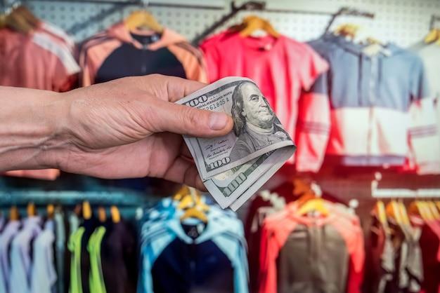 Vrouw maar nieuwe doek in winkel hand met dollar mode verkoop