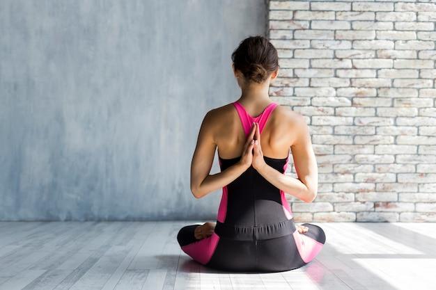 Vrouw maditating met handen gevouwen in namaste yoga pose