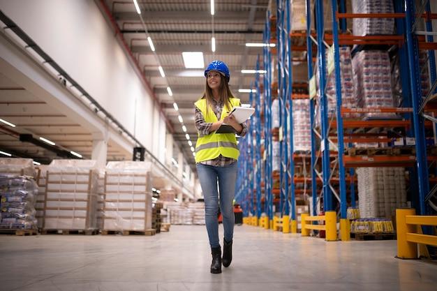 Vrouw magazijnarbeider zelfverzekerd wandelen door groot magazijn opslagcentrum en distributie organiseren
