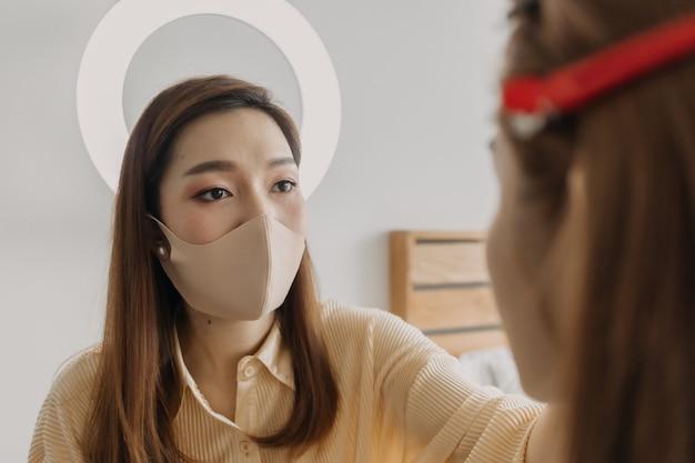 Vrouw make-up artist is aan het werk en het dragen van make-up op haar model.
