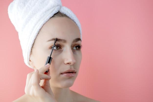 Vrouw make-up. close-up van jonge vrouwelijke model face met gladde zachte gezonde huid en frisse make-up. mooie meisjeshand met wenkbrauwgelborstel voor wenkbrauwen. schoonheidstools.