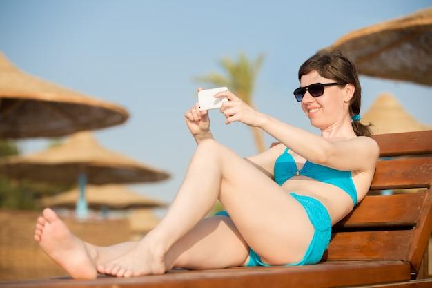 Vrouw maken foto op mobiele telefoon op houten ligstoel