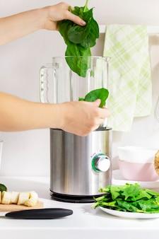 Vrouw maken groene spinazie detox smoothie met appel en kiwi met behulp van een blender. gezonde levensstijl