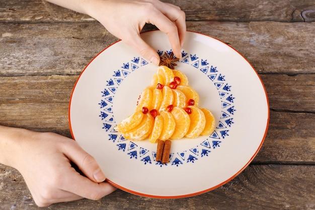 Vrouw maken kerstboom gemaakt van mandarijnen op oude houten tafel