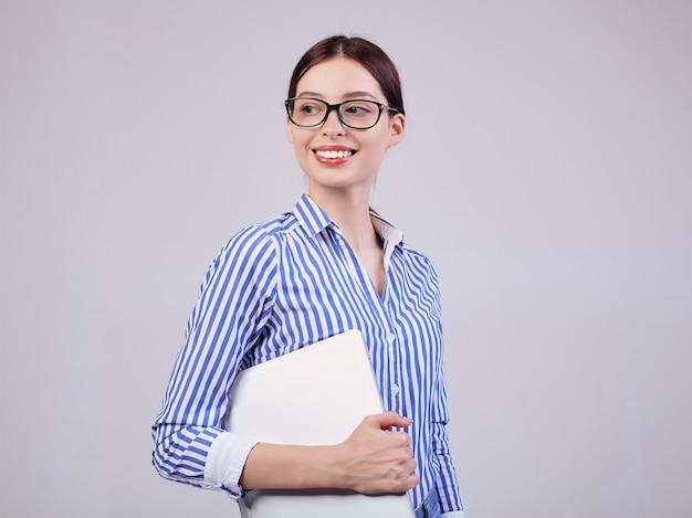 Vrouw manager in een gestreept wit-blauw shirt met bril en een laptop op grijs. werknemer van het jaar, zakelijke dame.
