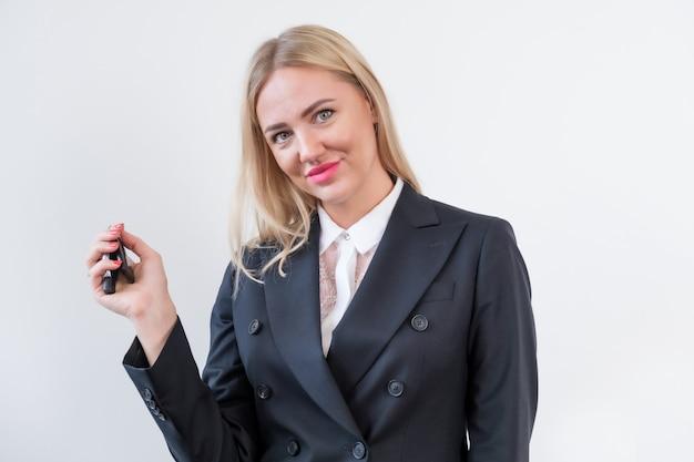 Vrouw manager in zakelijke kleding houdt de sleutels van de auto vast en glimlacht terwijl ze naar de camera kijkt