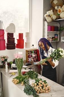 Vrouw manager permanent op de werkplek. dame met plant in handen. famale snijbloemen. bloemist concept.