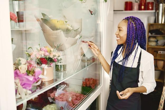 Vrouw manager permanent op de werkplek. dame met plant in handen. gelukkige vrouwelijke bloemist in bloemencentrum bloemistconcept.