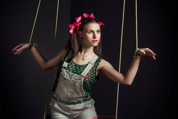Vrouw marionet handen gebonden poseren. mode kunst