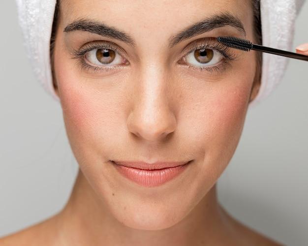 Vrouw mascara toe te passen op haar wimpers close-up